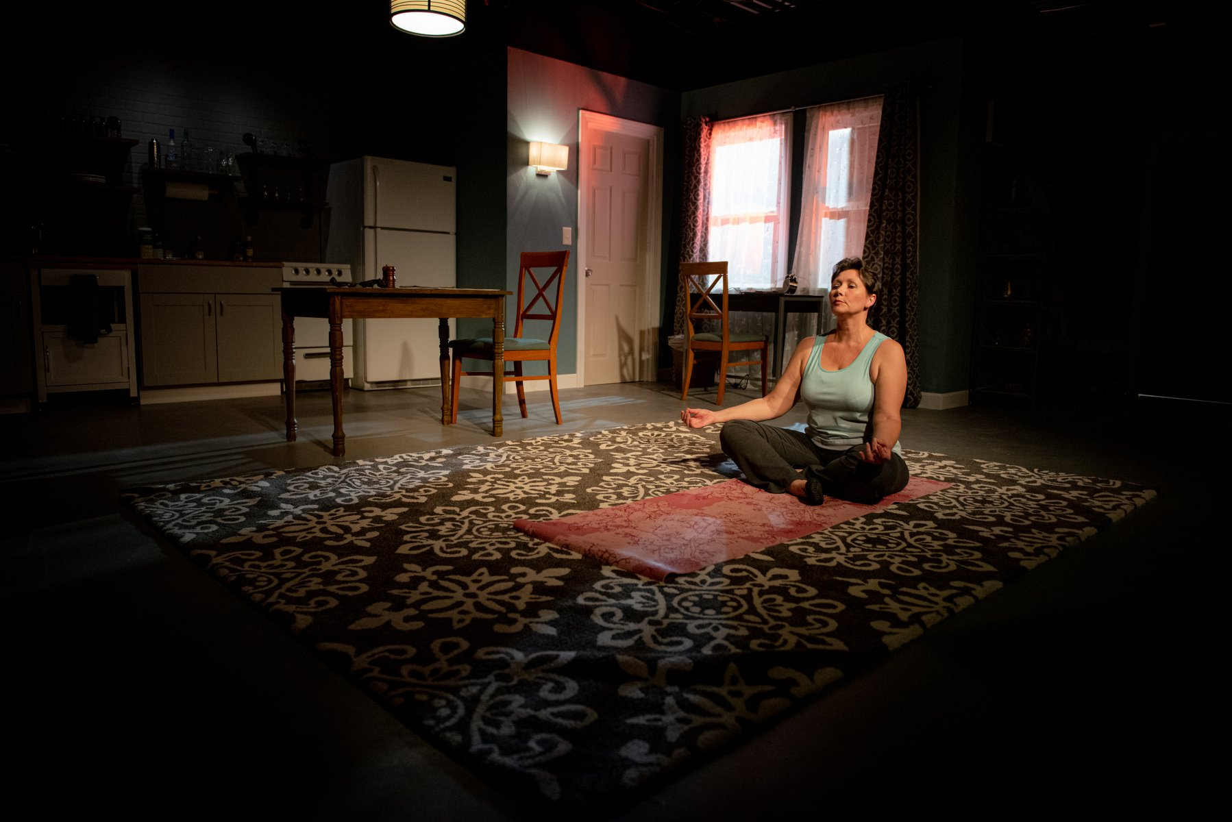 The protagonist meditating in a dark room.